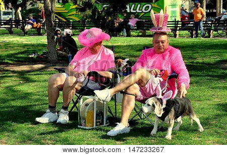 Washington DC - April 11 2014: Two gentleman wearing colourful pink shirts and Cherry Blossom Festival hats with their dog sporting Easter Bunny ears at Dupont Circle