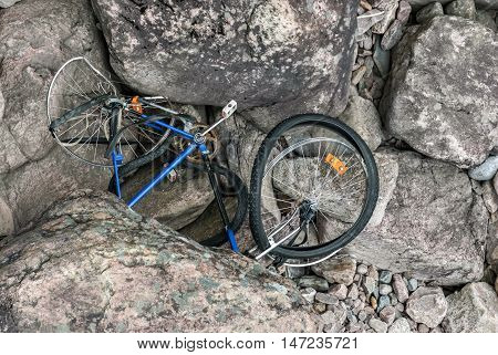 Broken bicycle lying on the rocky bottom of a dried-up riverbed.