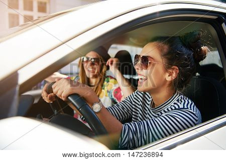 Laughing trendy young girlfriends in sunglasses traveling in a car in town with focus to the profile of an attractive young woman through the open window