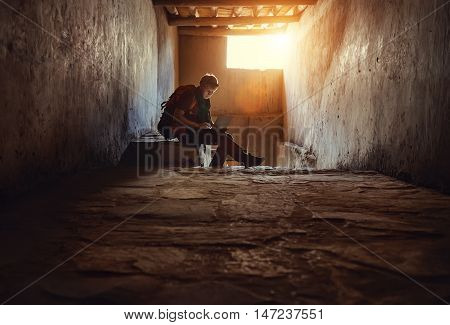 Young man tourist sits with laptop in old tibetan palace
