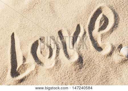Love, word - written by hand in sand on a sea beach, Valentines Day