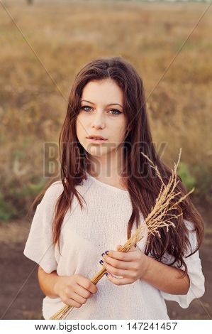 Young girl with long brown hair holds a bundle of ears in her hands and looks happily. Selective focus warm tinted.