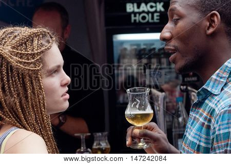 BELGIUM, BRUSSELS - SEPTEMBER 07, 2014: Belgian Beer Weekend 2014. The most famous beer festival in Belgium. A girl and a guy with a glass of beer at the festival.