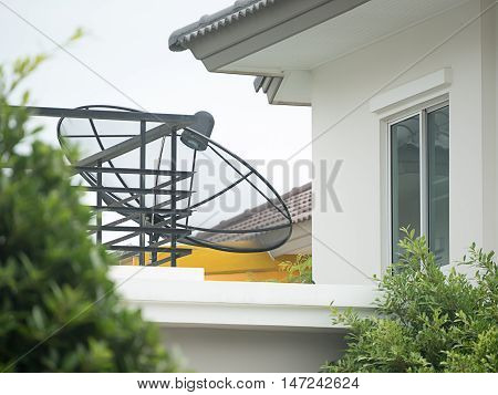 Black satellite dish mounted on a wall outside the house. A drop of