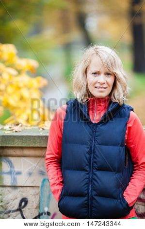 Young woman relaxing in autumn park. Caucasian blonde girl smiling and looking to a side in fall season park or woods leisure and recreation outdoors. Inspiring yellow autumn park.