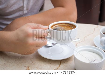 Man at marble table holds a cup of americano coffee in his hand
