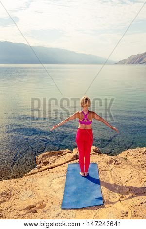 Woman meditating in yoga pose at the sea on rocks. Caucasian blonde girl exercising and training yoga stretching outside under cloudy morning sky. Fitness and exercising motivation and inspiration.