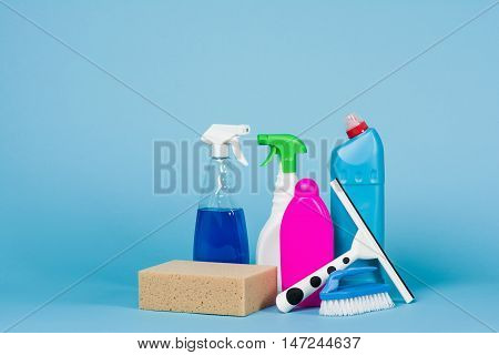 Cleaning concept - mixed detergents and cleaning accessories isolated on blue seamless background.