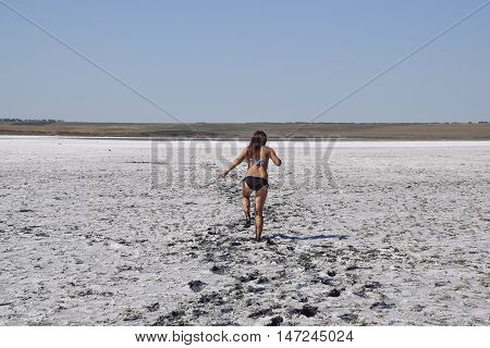 Woman Walking Along The Dry Bottom Of A Salt Lake, Rear View