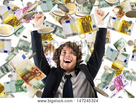 Happy businessman exults under a rain of coins and banknotes