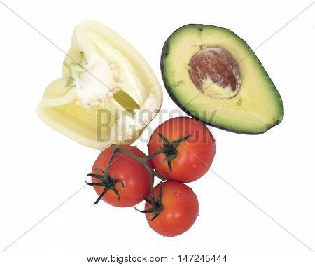 Ripe yellow gypsy pepper, avocado cut by half and tomatoes separated on white background