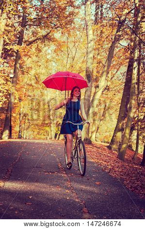 Gorgeous Girl Cycling With Umbrella.