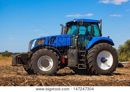Big blue tractor plows the field and removes the remains of previously mown sunflower. Work agricultural cleaning machines.