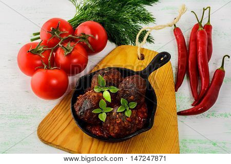 Grilled beef meatballs with chili pepper served in skillet. Grilled bbq meatloaf. Barbecue meatballs.