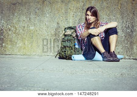 Man tourist backpacker relaxing outdoor sitting tired by grunge wall. Adventure summer tourism active lifestyle. Young hipster guy tramping