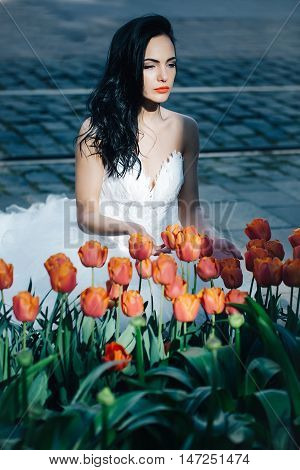young sexy woman or girl with long black brunette hair and pretty face in white wedding dress of bride sitting near flowerbed of red tulip flowers sunny day outdoor