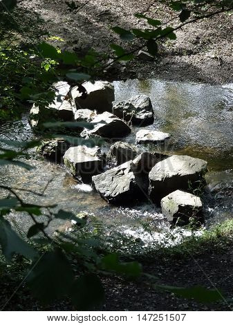 Stepping stones across river waterfall landscape photographed at Colby Woodland Garden near Amroth in Pembrokeshire