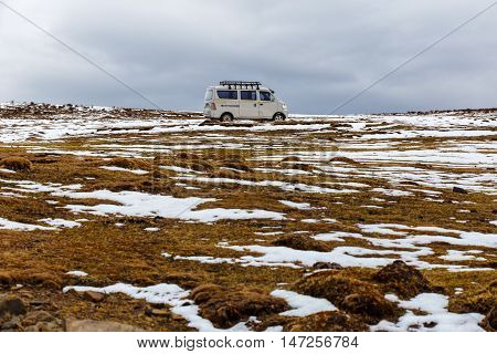 Old van on a deep snow under heavy snow way to the glacier Fjallsarlon Winter off road driving in Iceland