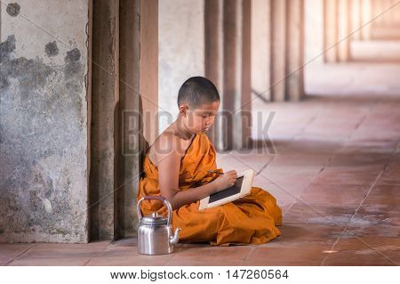 Little novice reading and studying blackboard with funny in old temple at sunset time Ayutthaya Province Thailand
