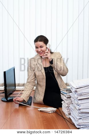 Young Caucasian Woman In Office Interior Calling By Telephone And Stack Of Paper Documents