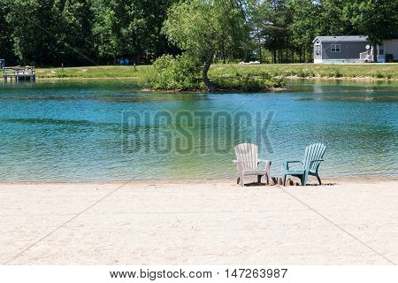 two empty Muskoka chairs set on the beach by some sandcastles in front of a pond