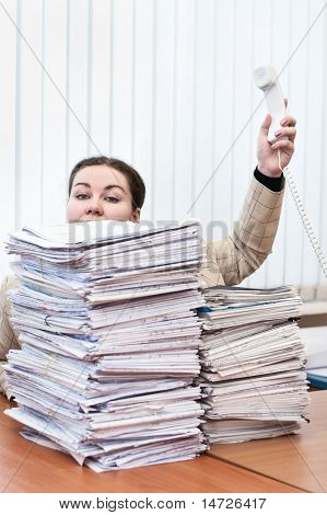 Telephone Handset In Hand Of Young Caucasian Woman Behind Pile From Paper Documents