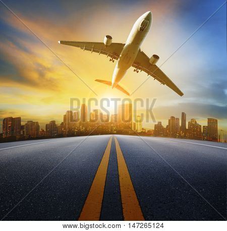 road perspective to town and passenger plane flying aboveair traveling and transport theme