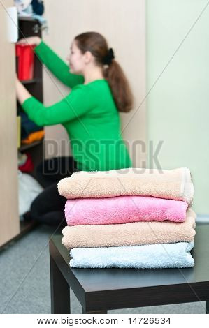 Stack Of Clothes And Young Caucasian Woman Arranging Things In The Wardrobe On Background.