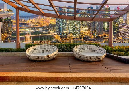 Relax corner on condominium rooftop garden with chairs on Landscape of the Singapore financial district and business building background Landmark concept