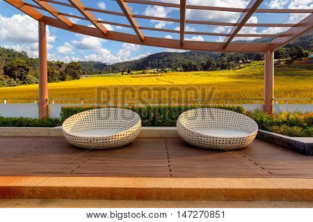 Relax corner on condominium rooftop garden with chairs on Green Terraced Rice Field in Pa Pong Pieng at Chiang mai background Relaxing concept