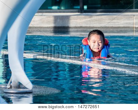 Asin Boy In A Swimming Pool Wearing A Life Vest, In Sunset Light