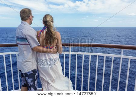 Happy Married Couple on a cruise together. Looking at their ocean view from a balcony while on a cruise ship vacation together