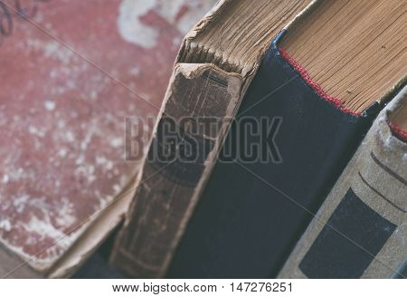 Stack of old tattered books close up. Selective focus