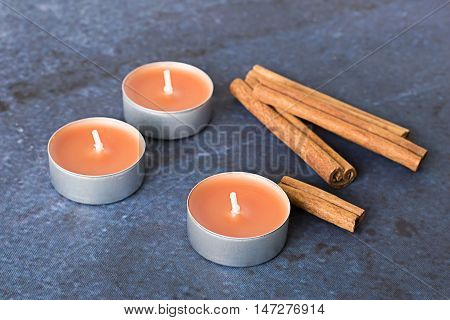 Cinnamon sticks and decorative candle with aroma of cinnamon on a blue background.