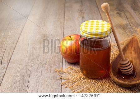Honey jar over wooden background. Jewish Rosh hashana (new year) celebration