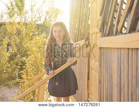smiling little girl standing on wooden porch of a seaside cabin