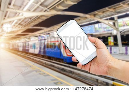 Female hand holding mobile smartphone tablet cell phone over Blurred abstract background of people on the Transit train in Bangkok Thailand