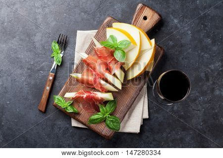 Fresh melon with prosciutto and basil. Antipasti and red wine. Top view on dark stone table