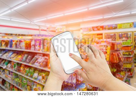 Female hand holding mobile smartphone tablet cell phone over blurred photo of department store shopping mall center and people background