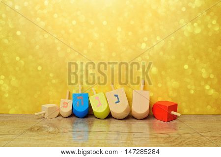 Jewish holiday Hanukkah background with spining top dreidel over gold bokeh. Copy space for text