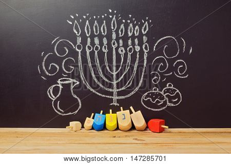 Creative Jewish holiday Hanukkah background with spining top dreidel over chalkboard with hand drawing