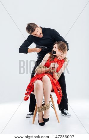 Criminal man threatening scared woman by gun isolated on the white background
