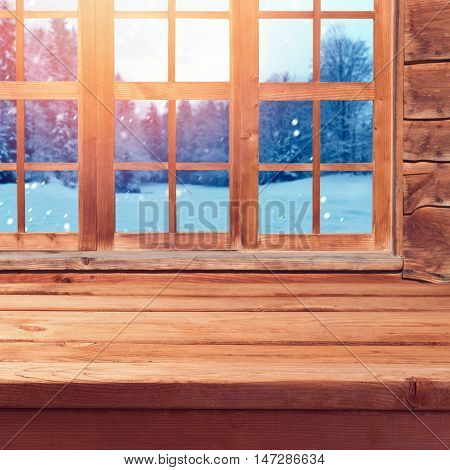 Christmas background with wooden empty table over window and winter nature lanscape. Winter holiday wooden house interior