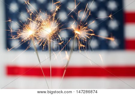 american independence day, patriotism, holidays and celebration concept - close up of sparklers burning over american flag
