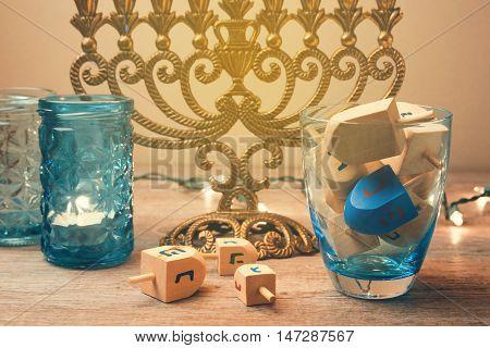 Jewish holiday Hanukkah celebration with spinning top dreidel. Retro filter effect.