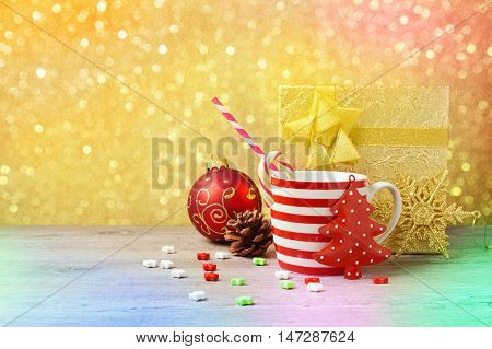 Christmas decorations and cup on wooden table over gold bokeh background