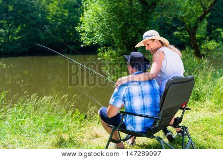 Man and woman fishing with angle together at river shore