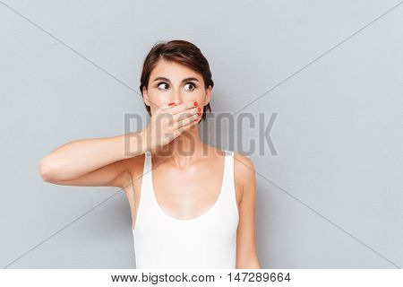 Young woman covering her mouth with palm isolated on a gray background
