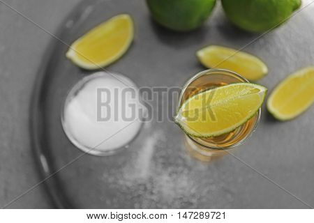 Shot of gold tequila with lime slices and salt on a tray