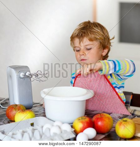 Adorable funny blond little kid boy of four baking apple cake and muffins in domestic kitchen. Happy child having fun with working with mixer, flour, eggs and fruits at home.